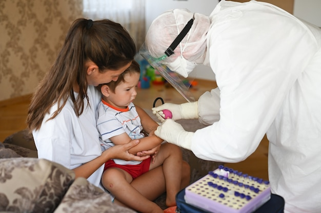 The doctor takes a blood test from the child at home
