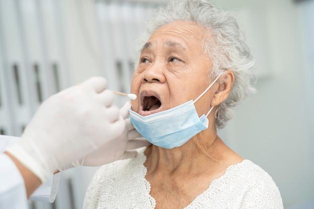 コロナウイルス感染をテストするためにアジアのシニア女性患者から喉と鼻腔スワブを取る医師