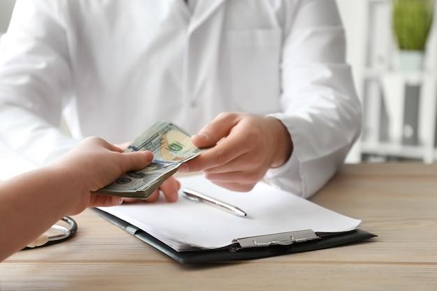医者はテーブルで女性から賄賂を取ります。