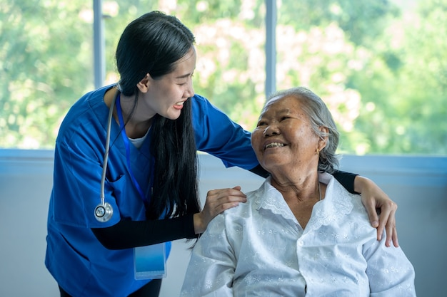 病院で年配の女性のケーキを取る医師、アジアの女性医師が世話をし、病院で年配の患者と話し合う、ヘルスケアと共感の概念。