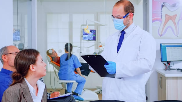 Doctor taking notes on clipboard about patient dental problems sitting on chair in waiting room of stomatological clinic. assistant preparing old woman for examination in background