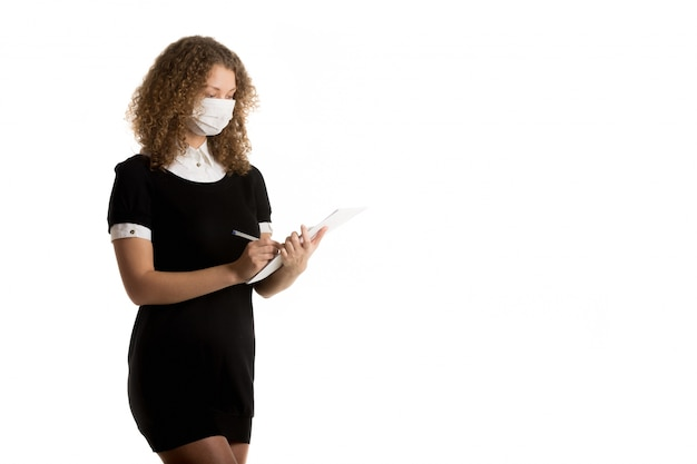 Doctor taking notes with her mouth covered with a mask