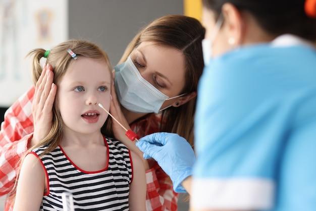 Врач берет мазок из носа маленькой девочки с помощью ватного тампона в клинике
