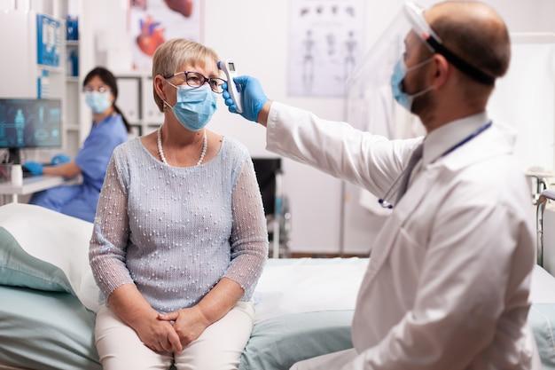 コロナウイルスの予防として年配の女性患者の体温を測定する医師