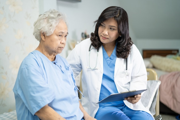 Doctor talking about diagnosis and note on clipboard with asian senior or elderly old lady woman while lying on bed in nursing hospital ward, healthy strong medical concept.