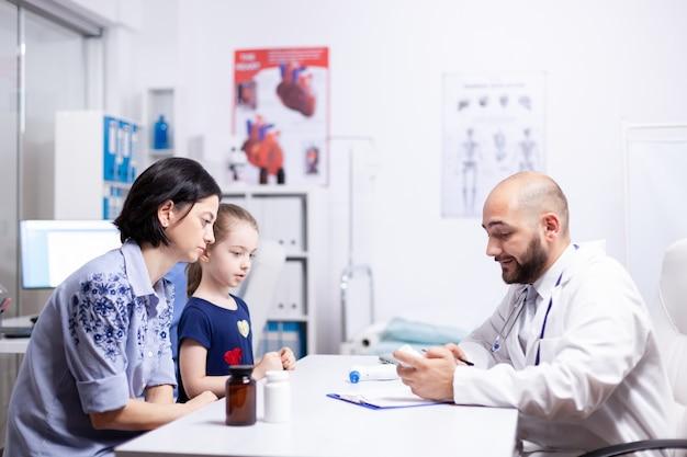 의사는 병원 사무실에서 아이의 어머니와 진단 및 치료에 대해 이야기합니다. 의료 서비스 치료 검사를 제공하는 의학의 의료 의사 전문가.
