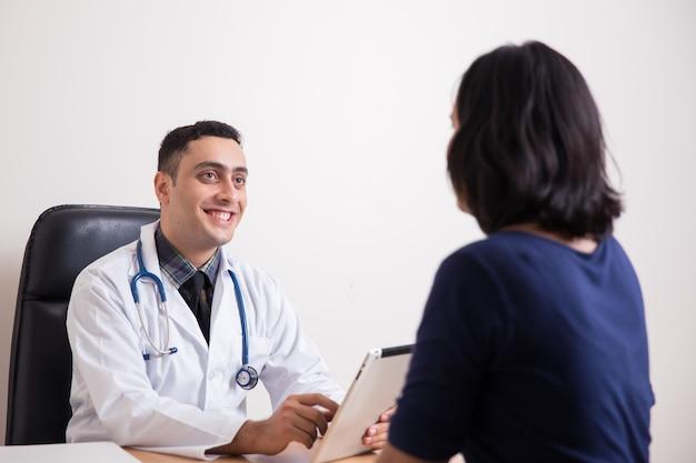 의사 사무실에서 여성 환자와 이야기하고 웃는 의사