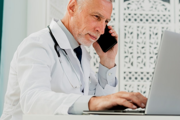 Doctor talking on his phone and using laptop