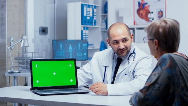 녹색 화면과 그것을 보고 있는 노인 환자가 있는 노트북 근처에서 의사가 이야기하고 있습니다. 앱 또는 광고에 대한 크로마 키 키잉을 제거할 준비가 된 모형 모형 격리 배경