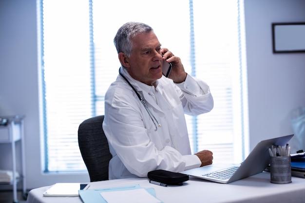 Доктор разговаривает по мобильному телефону во время использования ноутбука
