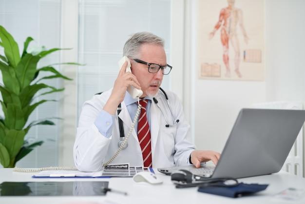 彼のスタジオで電話で話している医者