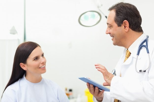 Doctor talking to a patient while holding a tablet tactile