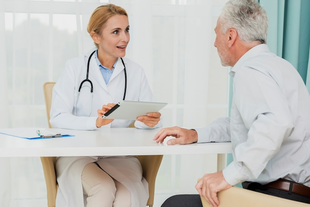 Doctor talking to patient while holding tablet