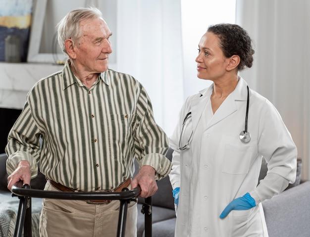 Доктор разговаривает со старшим мужчиной в помещении