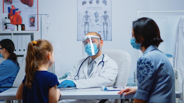 Доктор разговаривает с девушкой в медицинском кабинете и отмечает симптомы на ноутбуке. медицинский специалист в защитной маске, предоставляющий медицинские услуги, консультации, лечение в больничной клинике.