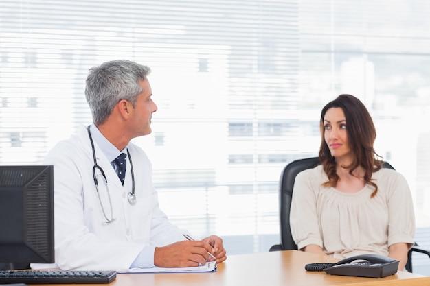 Доктор разговаривает со своим пациентом и пишет на ноутбуке