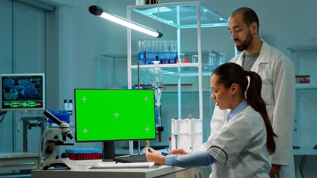 Доктор разговаривает с лаборантом и работает с зеленым макетом экрана настольного компьютера. исследователь лаборатории человек обсуждает с врачом о разработке вакцины, глядя на образцы крови