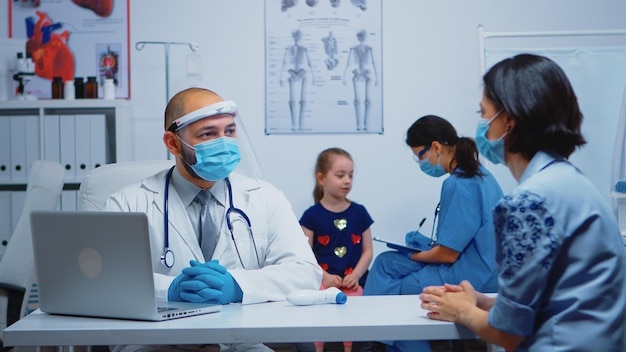 보호 마스크를 쓰고 간호사가 상담하는 동안 의사는 부모와 이야기합니다. 병원 캐비닛에서 의료 서비스 상담 치료 검사를 제공하는 의학 전문 의사.