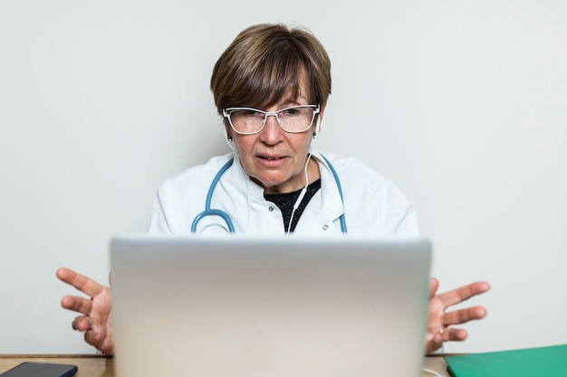 ノートパソコンでビデオ通話を介して患者と話し、医療アドバイスを与える医師。遠隔医療の予約