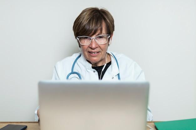 ノートパソコンのビデオ通話で患者と話している医師