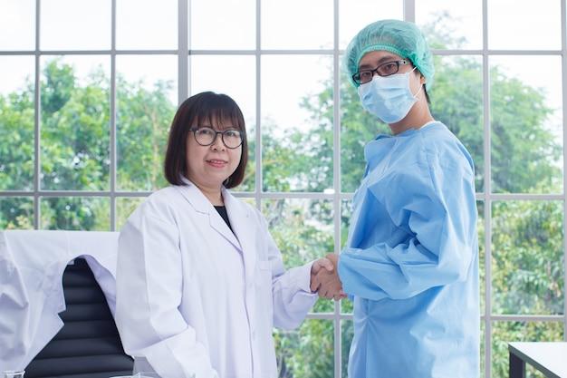 Команда доктора носит бело-голубую форму рукопожатия в лаборатории