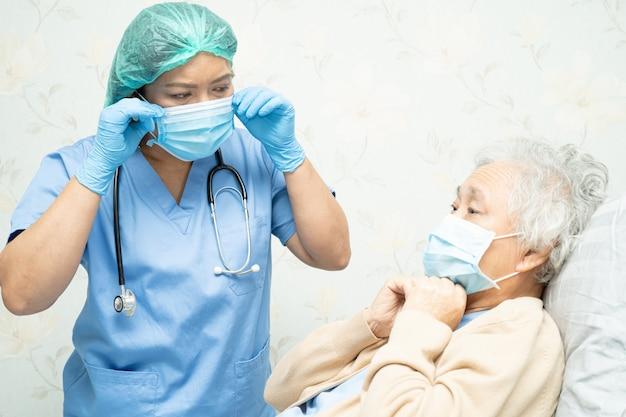 医者はcovid-19コロナウイルスを保護するために病院でマスクを身に着けているアジアの年配の女性患者をtechingします。