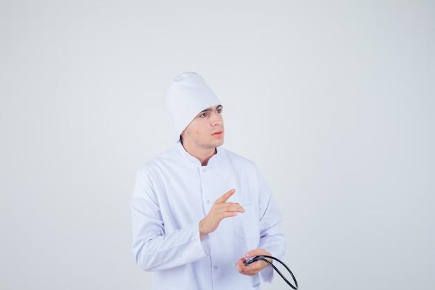 청진 기 유니폼을 누른 사려 깊은, 전면보기를 찾고 멀리 가리키는 의사 십 대 소년.