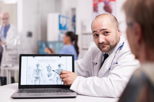 의사는 병원 사무실에서 방사선 검사를 하는 동안 허리 수술이 필요하다고 노인 환자에게 말합니다. 백그라운드에서 엑스레이를 들고 파란색 유니폼에 간호사. 클리닉 복도에 있는 노인 의사.