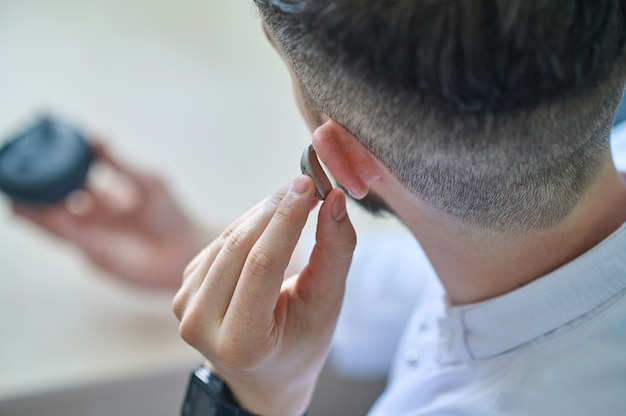 Doctor testing hearing aid in his ear