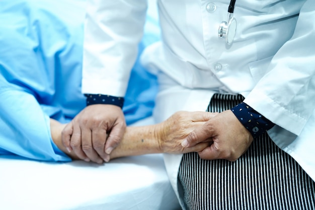 Doctor touching hand asian elderly old lady patient with love, care