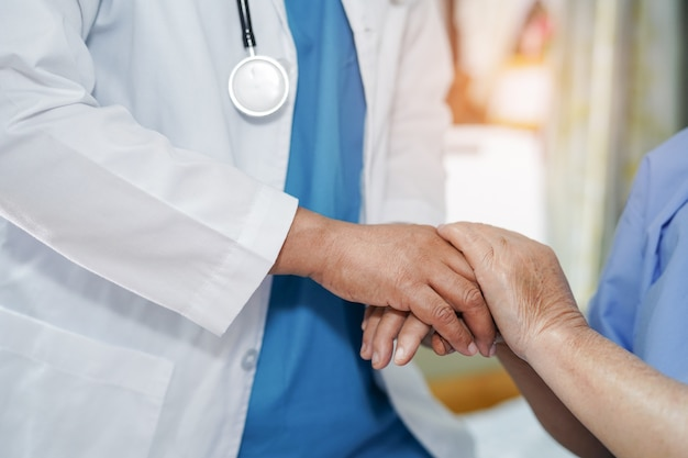 Doctor touching hands asian senior or elderly old lady woman patient with love