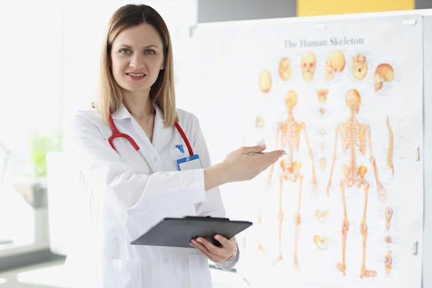 Doctor traumatologist holding medical documents and showing with his hand to poster with human skeleton