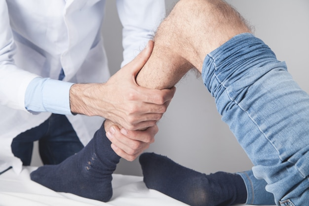 Doctor treat the knee to the patient.