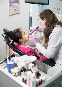 歯科医院で患者の女の子の歯を治療する医師