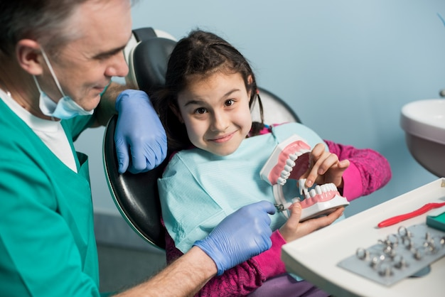 Doctor treating patient girl teeth at dental office