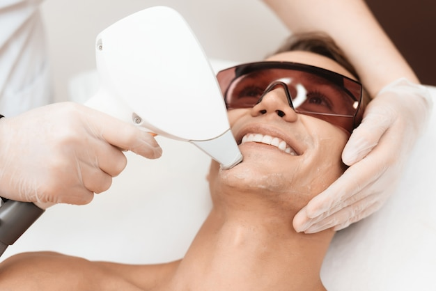 Doctor treats the face of a man with a modern laser epilator