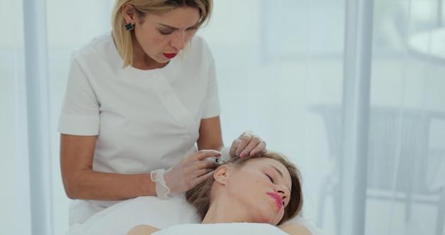 Врач-трихолог делает инъекции мезотерапии с витаминами в кожу головы женщины для роста волос и против перхоти в косметологической клинике.