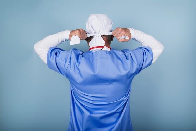 외과 모자를 묶는 의사