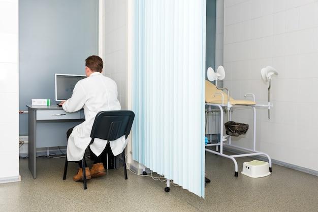 Врач печатает и использует свой компьютер в офисе