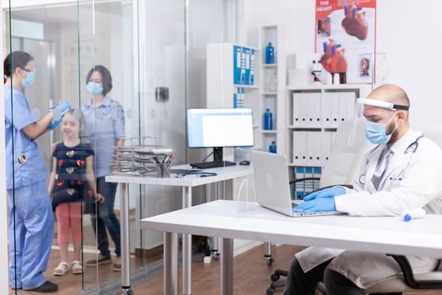 코로나바이러스 전염병에 대한 보호 장치를 착용하고 병원 사무실에서 노트북에 타이핑하는 의사. 의사, 의료 서비스, 상담을 제공하는 보호 마스크가 있는 의학 전문가.