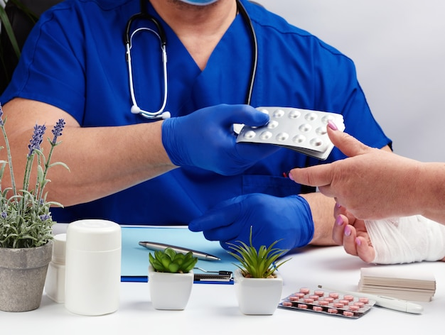 Doctor in uniform and blue latex medical gloves sits at a table and examines a patient with a hand injury