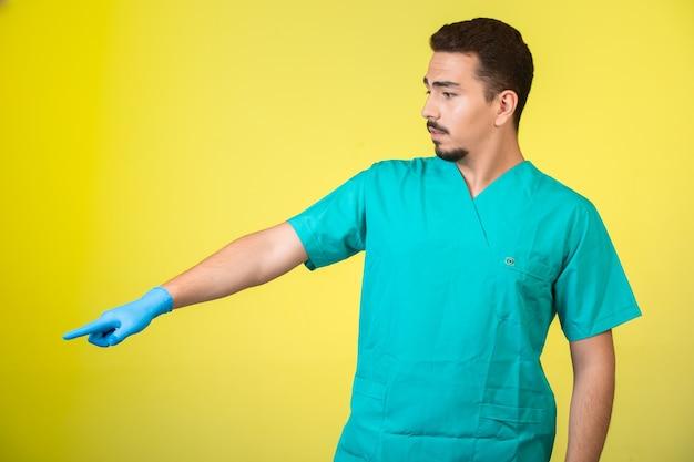 Dottore in uniforme e maschera per le mani che mostra qualcosa da parte.