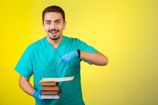 Dottore in uniforme e maschera per le mani in piedi e indicando i suoi libri che significano la sua educazione.