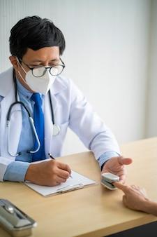 Врач использует пульсоксиметр с зажимом для пальца - медицинское оборудование для проверки пульса на коронавирус или сердцебиение пациента с covid-19 в больнице. медицинское оборудование, концепция вспышки коронавируса