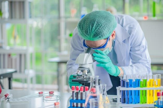 Доктор использует микроскоп на коленях в больнице, ученый тестирует исследовательскую вакцину в химической лаборатории