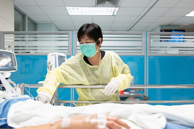 Doctor use monitor with vital signs for medical care of the flu covid, corona virus, cre. or vre. infected elder patient on patient bed in intensive care unit (icu.)