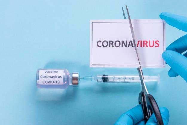 医師は、「コロナウイルス」カードのテキストからウイルスをカットするハサミを使用します。 covid-19アウトブレイクコンセプト。