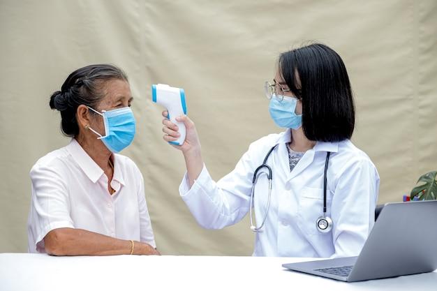 의사는 노인 환자의 체온을 측정하기 위해 발열 측정기를 사용했습니다.