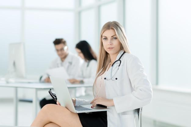 의사는 노트북을 사용하여 문서 작업을합니다.