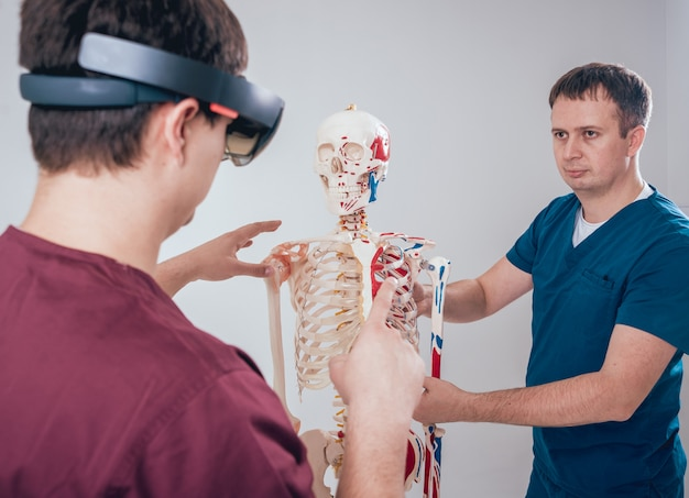 Doctor uses augmented reality goggles and human skeleton for teaching student